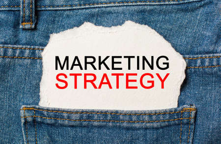 Marketing Strategy on torn paper background on jeans business and finance concept