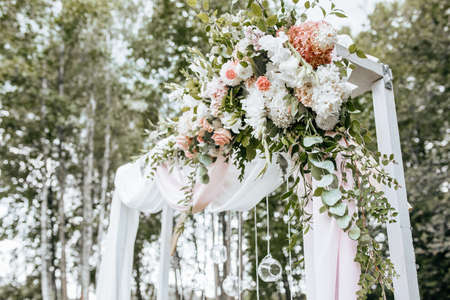 Decorating the arch with flowers and fabric for a wedding ceremony in nature