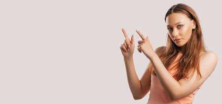 Portrait of a smiling girl pointing finger to the side at on a white isolated background. Positive woman points to an idea, a place for advertising