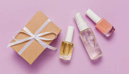 Organic cosmetics and gifts for the holiday. Flat lay, top view clear glass pump bottle, brush jar, moisturizing serum jar on a purple background. Natural cosmetics SPA