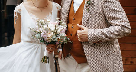 Bride and groom on wedding day hug and show love with a wedding bouquet of rose flowers