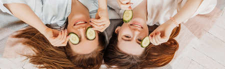 Two girls make homemade face and hair beauty masks. Cucumbers for the freshness of the skin around the eyes. Women take care of youthful skin. Girlfriends laugh at home lying on the floor on pillows. 版權商用圖片
