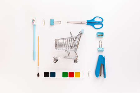 Top view of modern white blue office desktop with school supplies and stationery on table with basket or shopping trolley. Back to school concept flat lay with mockup