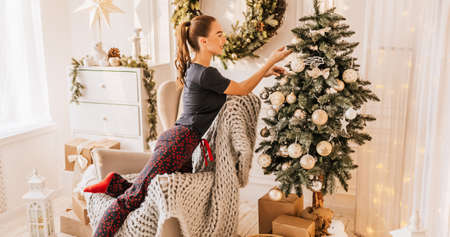 Beautiful cheerful happy young girl with christmas gifts on sofa on the background of a new year tree at home