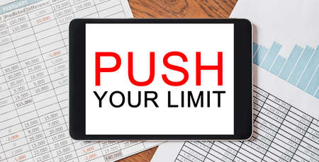 Tablet with text PUSH YOUR LIMIT on your desktop with documents, reports and graphs. Business and finance concept 版權商用圖片