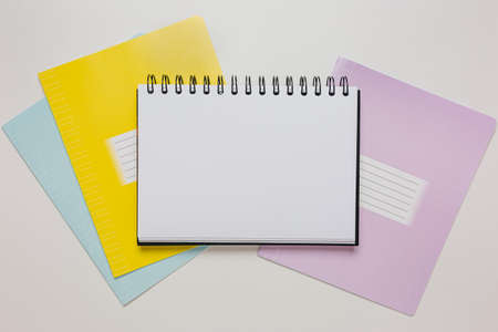 Notepad and exercise book on the desk. Mock up in copy space office on white background. Back to school