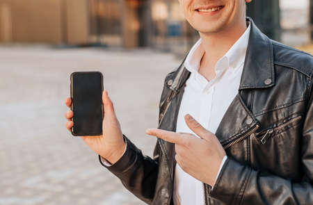 Handsome with a smartphone on the street of a big city. Businessman points finger at phone screen on urban background 版權商用圖片