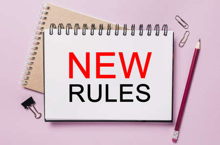 Text new rules on a white sticker with office stationery background. Flat lay on business, finance and development concept