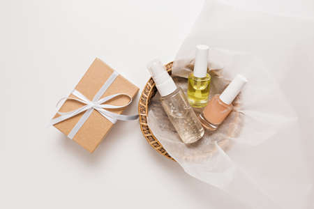 Organic cosmetics and gifts for the holiday. Flat lay, top view clear glass pump bottle, brush jar, moisturizing serum jar in a paper basket on a white background. Natural cosmetics SPA
