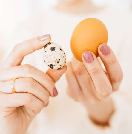 Woman holds chicken and quail eggs in her hands. Protein in food, concept of healthy food, vitamins and nutrients