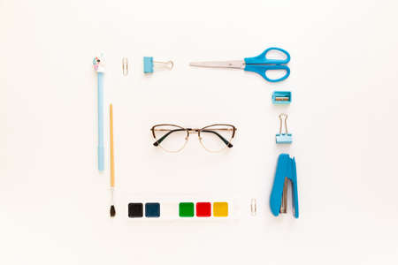 Top view of modern white blue office desktop with school supplies and stationery on table with glasses. Back to school concept flat lay with mockup