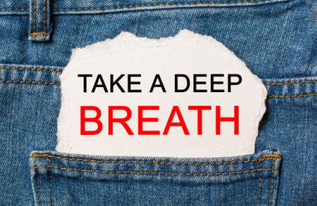 Take a deep breath on torn paper background on jeans business and finance concept