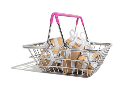 The gift lies in a shopping basket on a white isolated background. Holiday concept of celebration and congratulations, shopping and preparation for the event 版權商用圖片