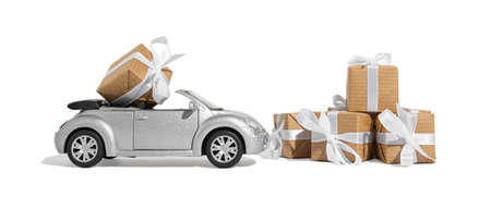 Silver convertible car carrying a gift for the holiday on a white isolated background. New year and christmas concept