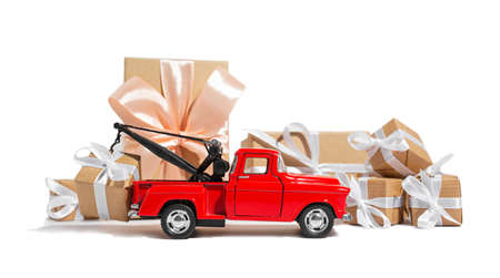 Red pickup car carrying a gift for the holiday on a white isolated background. New year and christmas concept 版權商用圖片