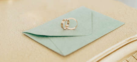 Two wedding rings lie on an invitation with gold background