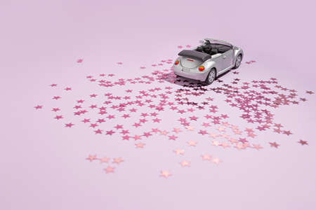 Silver convertible car goes on holiday on a purple background. Valentine celebration and delivery concept