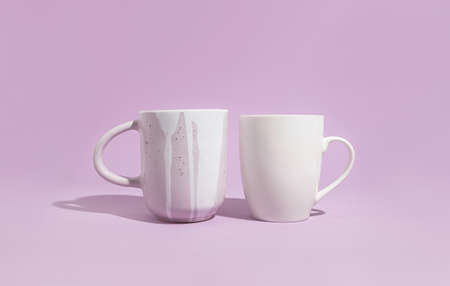Two designer mug on a solid purple background. Handmade ceramics concept