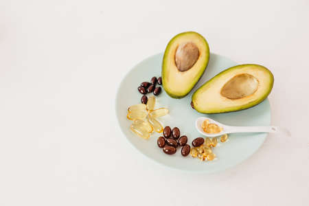 Health care and diet concept. Avocado and fish oil in capsules for vitamin D and omega-3 fatty acids in a plate on a white background