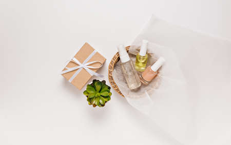 Organic cosmetics with plant and gifts for the holiday. Flat lay, top view clear glass pump bottle, brush jar, moisturizing serum jar in a paper basket on a white background. Natural cosmetics SPA