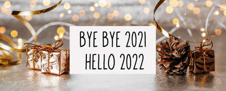 hello 2022 bye bye 2021 note with envelope, gifts and gold ribbon on white background