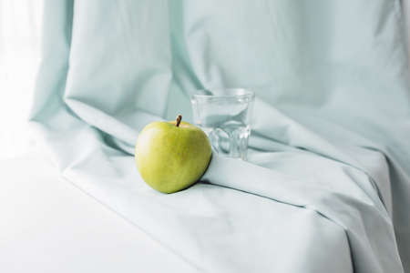 Green apple and a glass of water on a blue towel. Health care and diet concept