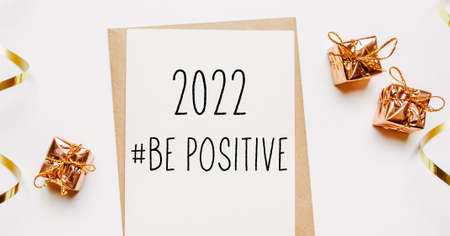 2022 be positive note with envelope, gifts and gold ribbon on white background