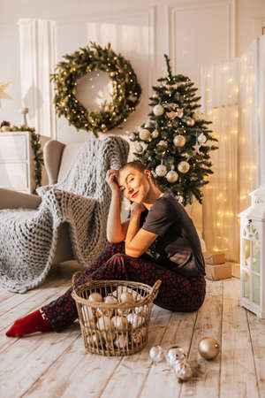 Beautiful cheerful happy young girl on the floor in pajamas with christmas toys near the new year tree at home