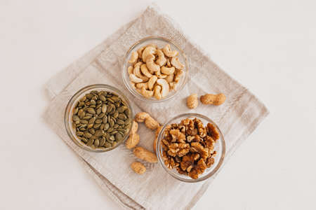 Nuts and vinegar on a linen tea towel on a white table. Walnuts, cashews and pumpkin seeds for proper nutrition. healthy foods and nutrients for the brain and body