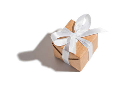 Gift tied with a white ribbon on a white isolated background. Celebration and congratulations holiday concept 版權商用圖片