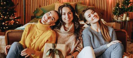 Three beautiful cheerful happy young girls girlfriend give Christmas gifts on the background of a new year tree at home