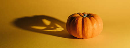 Halloween background concept. Jack O pumpkin angry face shadow. Spooky smiling shadow of an orange pumpkin lantern top view close up, Halloween party design