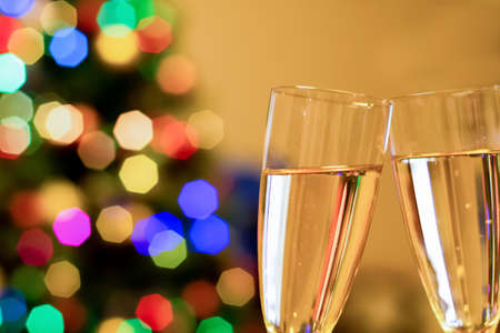 Blurred christmas tree and two glasses with sparkling wine champagne. New Year and Christmas Concept Imagens