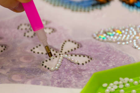 Diamond painting embroidery craft. Acrylic rhinestones and a pen. Closeup, selective focus