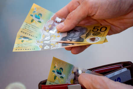 Hands holding wallet with australian dollars and make a payment - coronavirus finance struggle concept