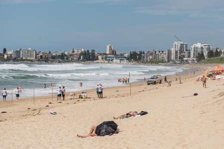 Sydney, Australia 2020-02-15 People sunbathing on Wanda beach on summer day. Surf rescue crew training.