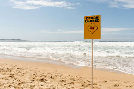 Beach closed sign at the sandy beach. Coronavirus outbreak leads to closure of some popular beaches in Australia
