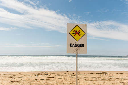 Danger sign for swimmers at the beach in Australia Foto de archivo