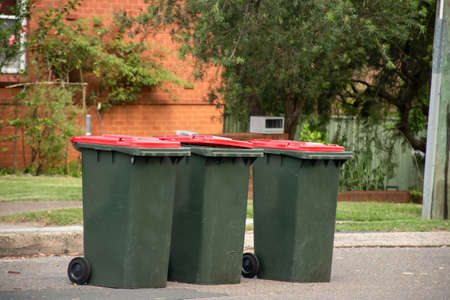 Australian garbage wheelie bins with red lids for general household waste lined up on the street kerbside for council rubbish collection. 版權商用圖片