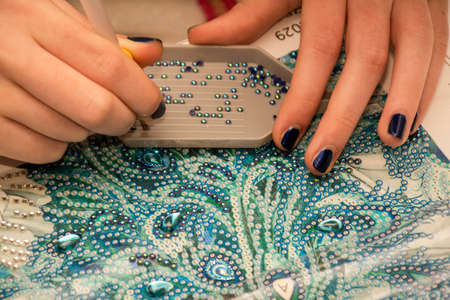 Diamond painting embroidery craft. Acrylic rhinestones and hand holding a pen. Closeup, selective focus.