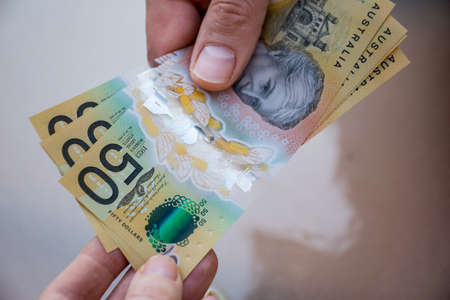 Hands holding australian dollars 50 banknotes. Finance help and payment concept
