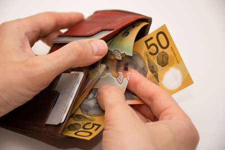 Hands holding leather wallet with australian dollars 50 banknotes. Finance and payment concept. Stock Photo