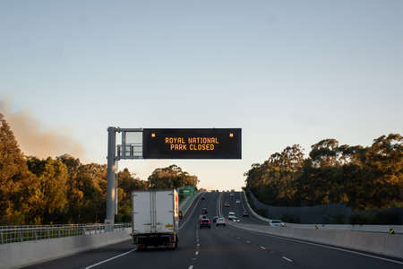 Sydney, Australia. 2020-10-10 An out of control bushfire has forced the closure of the Royal National Park in Sydney's south. Smoke from the bushfire is visible left over the road. 新闻类图片