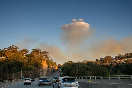 Sydney, Australia. 2020-10-10 Smoke from Royal National Park bushfire visible over the road. The blaze started when hazard reduction burning caused a spot fire which got out of control