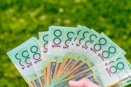 Hands holding australian dollars 100 banknotes on green grass background. Finance and payment concept.