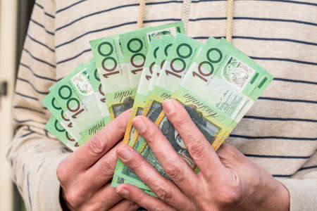 Hands holding australian dollars 100 banknotes. Finance and payment concept.