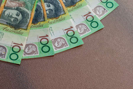 Australian dollars 100 banknotes on glass table background. Finance and payment concept. Фото со стока