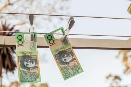 Australian 100 dollar bank notes hanging out to dry on a clothes line.