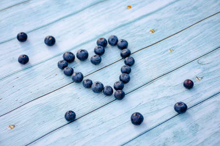 Superfood berries: blueberry heart on a wooden background