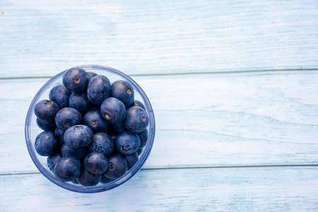 Superfood berries: blueberries in a bowl on a wooden background